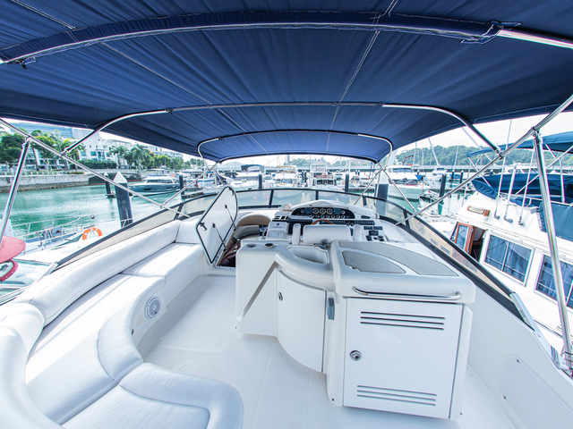 white interior yacht in singapore with long couch and blue topper