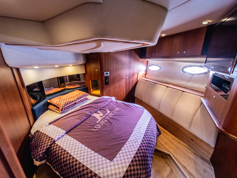 mini bedroom with louis vuitton bed and oval windows in singapore staycation yacht