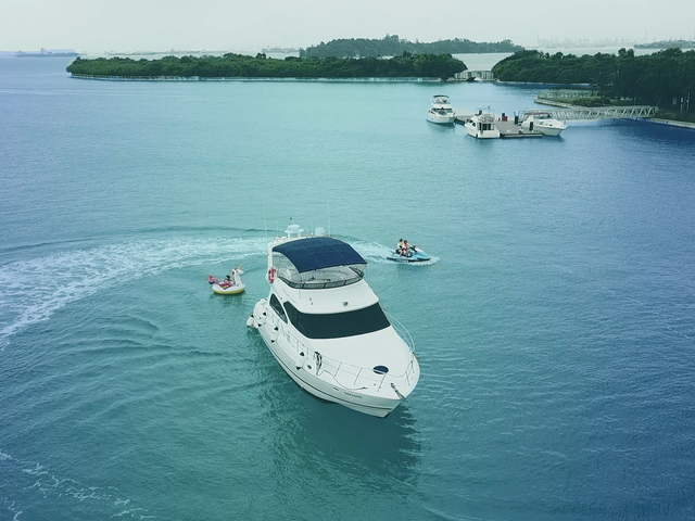 small white yacht in singapore with water sports activities