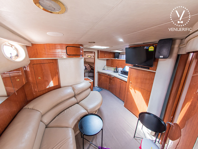 singapore party yacht with long couch and television on lower deck