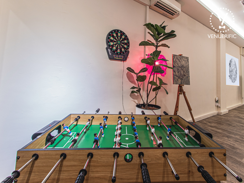 the foosball table with a high plant and dart in the background