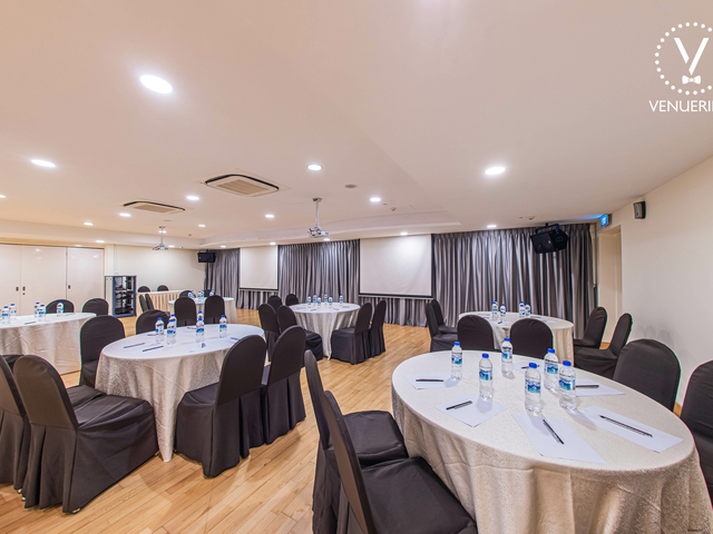 large seminar space in singapore with projector screens and round tables