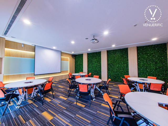 function room in singapore with projector screen and several round tables