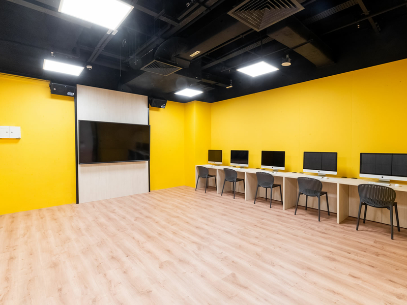 yellow workshop room in singapore with computer on each table and large tv screen