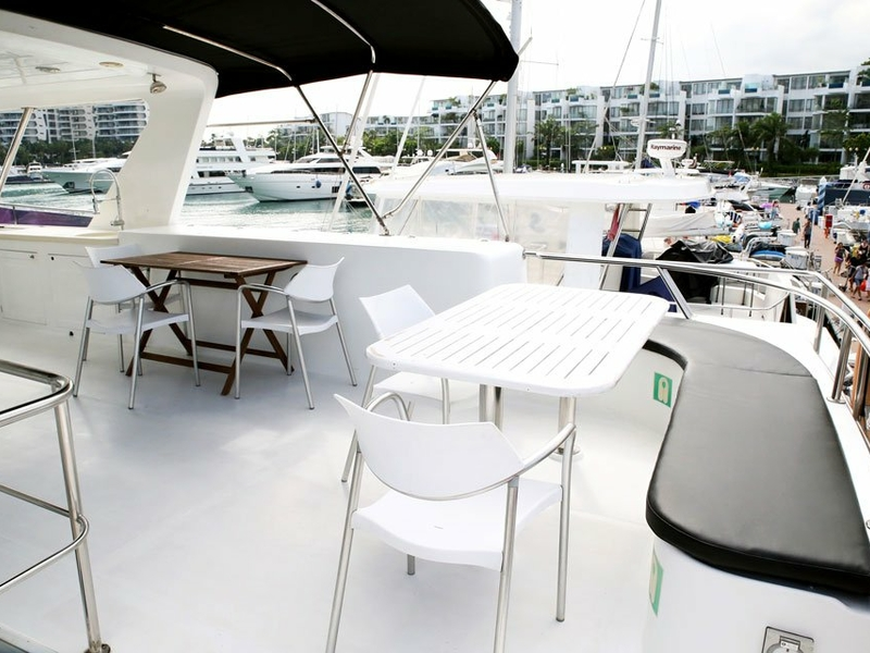birthday yacht in singapore with long chairs and large deck area