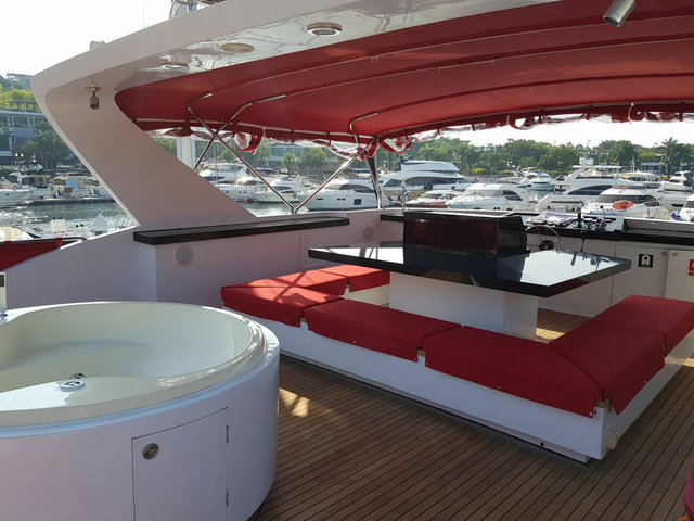 red u-shaped couches with jacuzzi in upper deck singapore party yacht