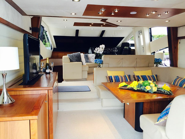 large yacht in singapore with several beige couches and television