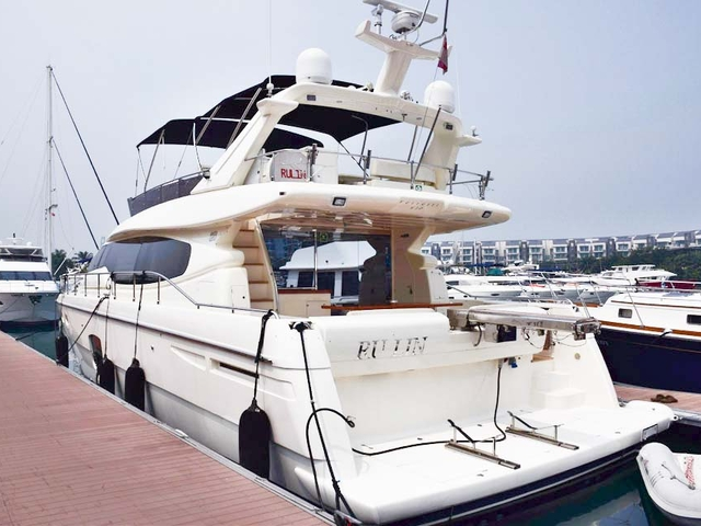 medium yacht in singapore with white interior and upper deck area