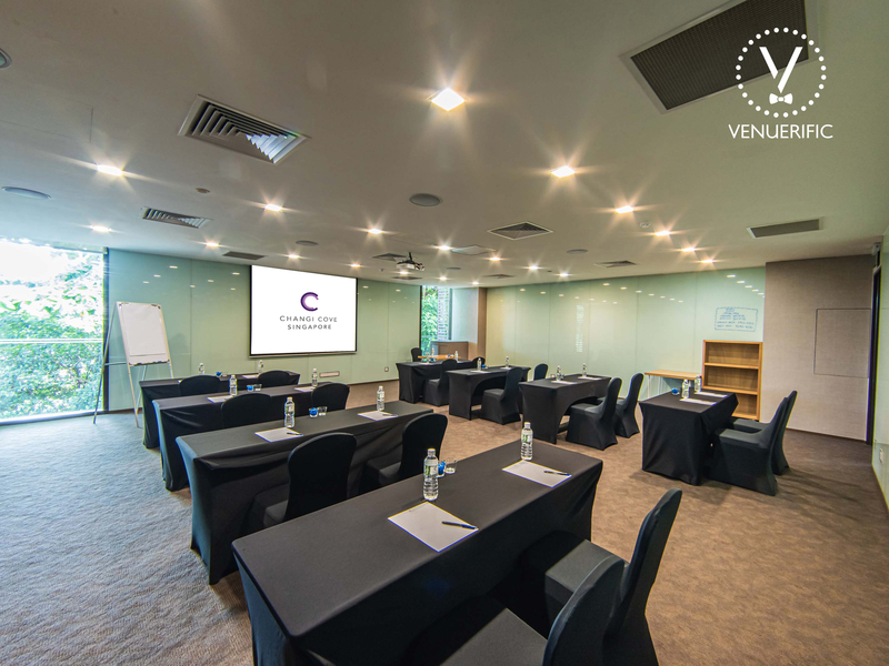 meeting room with classroom setup, flipchart, and screen projector
