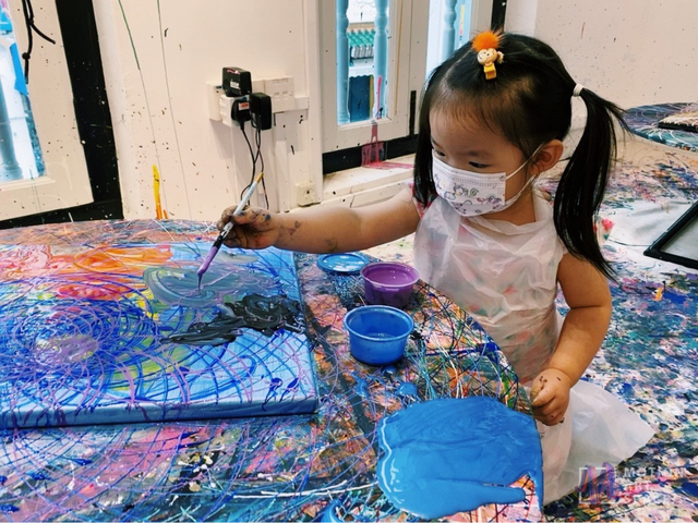a little girl is doing her own painting