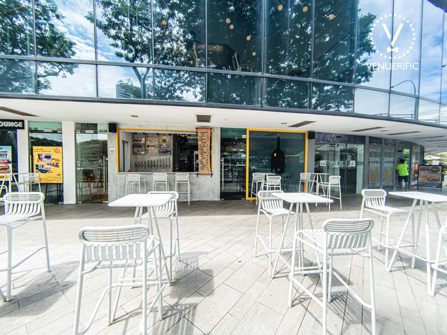 outdoor area of yeast side cafe with white high tables and chairs