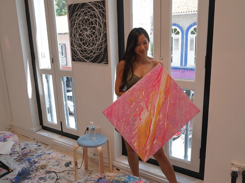 a girl is taking photo with her colourful canvas