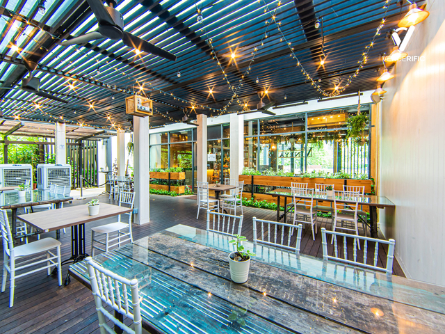 event space area with aged-wood tables and rustic earthly wood fixtures