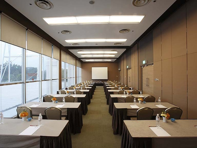 spacious meeting room with brown tables and chairs