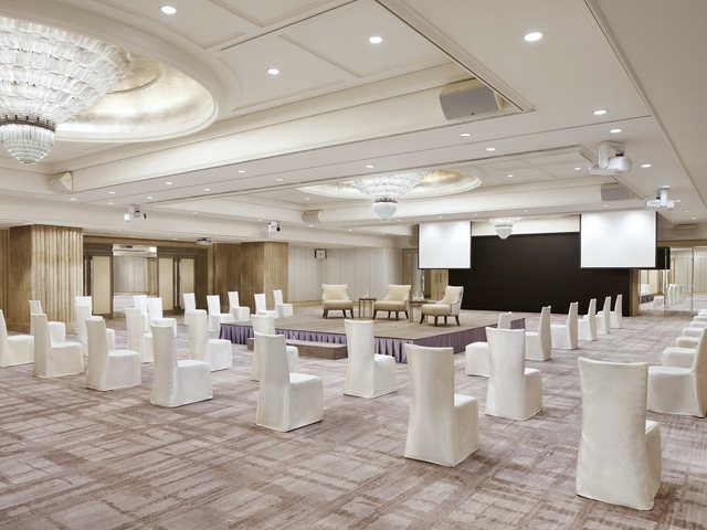 a spacious ballroom with white chairs and a stage