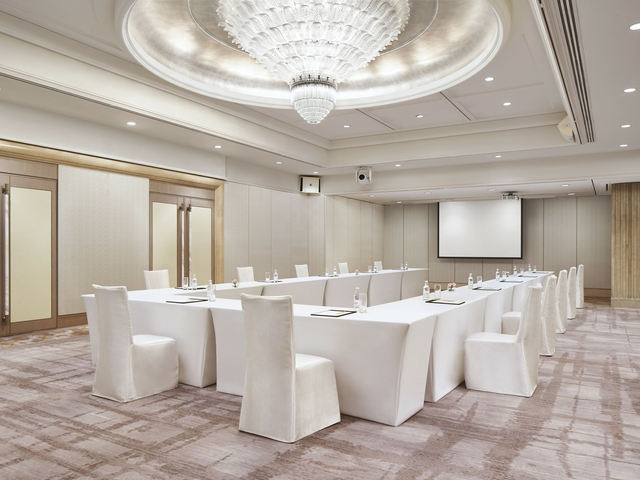 a large meeting room with white tables and chairs