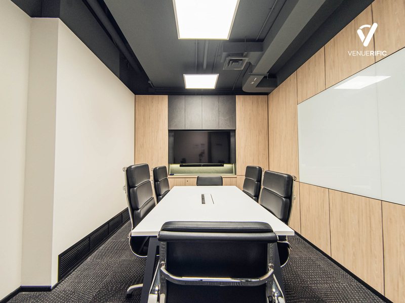 a meeting room with black office chairs and white table