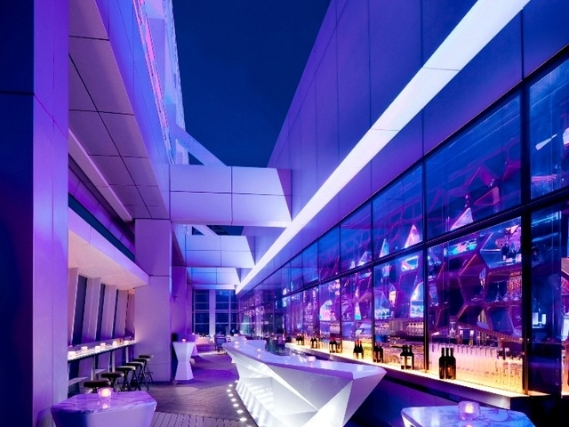 bar and event space with high ceiling and pruple theme of lighting
