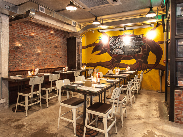 main dining space of brickhouse with a buffalo wallpaper on the brick walls