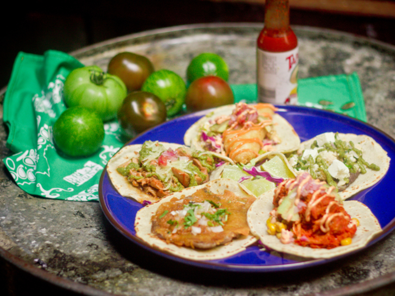tacos with different taste served on the plates with a bottle of sauce