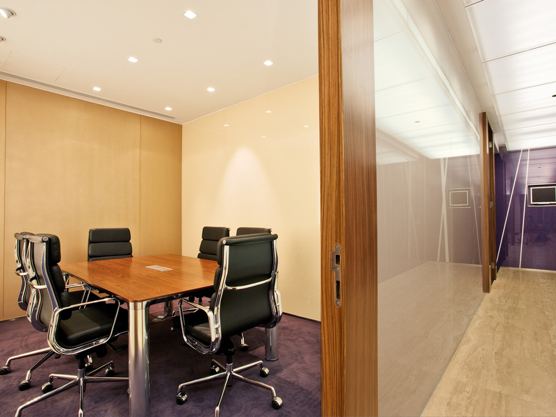 small meeting room using purple carpet and equipped with table chairs