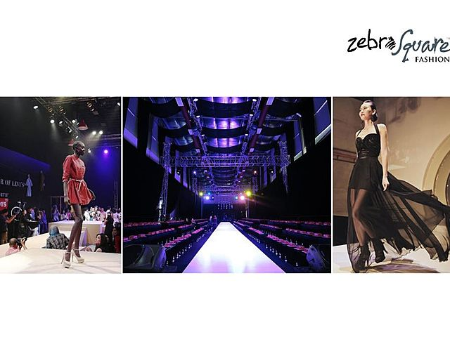 large fashion show event venue with black drape and long stage