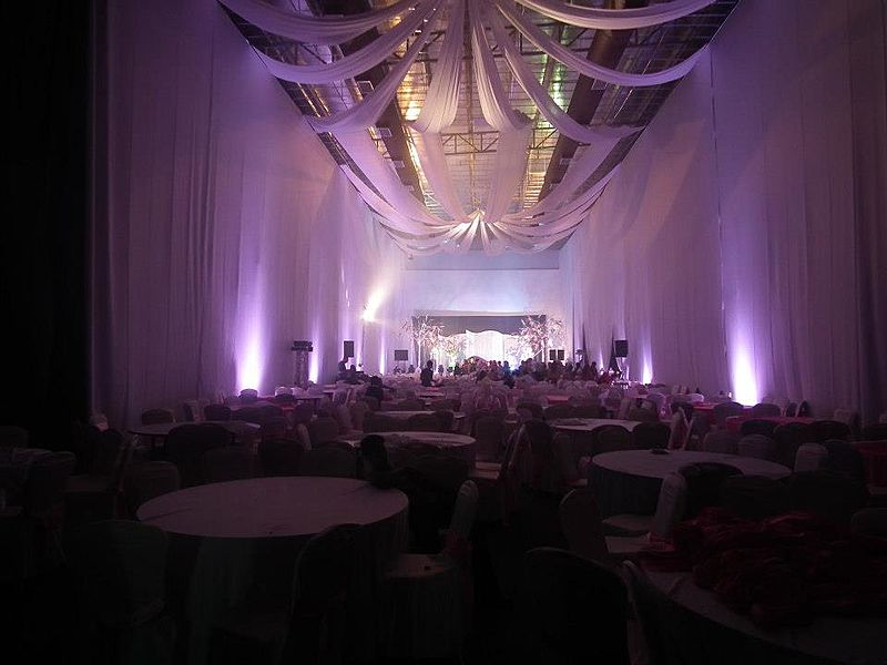 high-ceiling function hall with white drapes and banquet seating