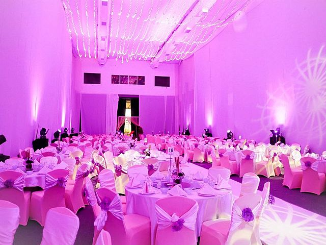 corporate dinner party venue with banquet seating and pink lighting