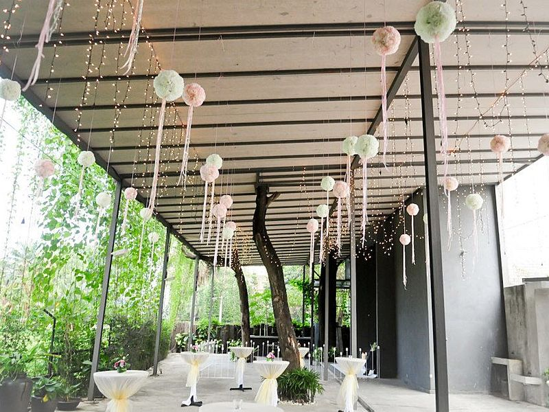 semi-outdoor event space equipped with cocktail table and colourful hanging decorations