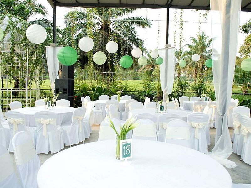 semi-outdoor venue decorated with white banquet seating and paper lantern lamp