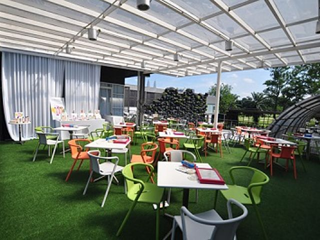 large semi-outdoor dining area with glass ceiling and grass floor