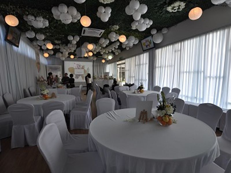 kuala lumpur function room with projector screen and white-themed decoration