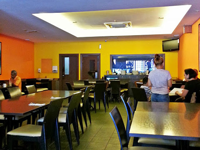 restaurant dining room with yellow wall and black furniture