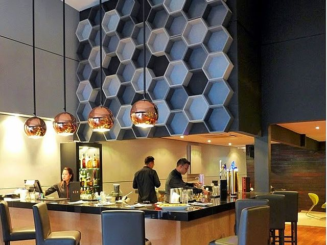 bar counter with round pendant lights and hexagon patterned wall