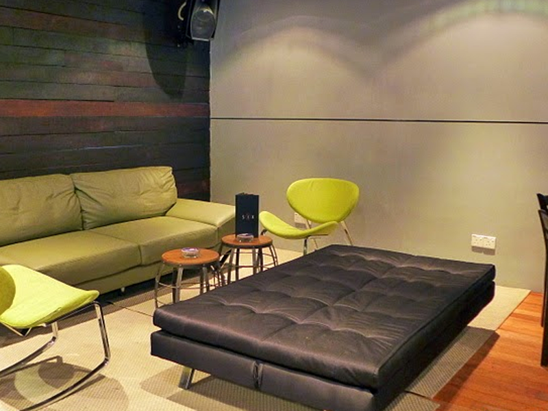 event venue area equipped with speakers and black folding couch