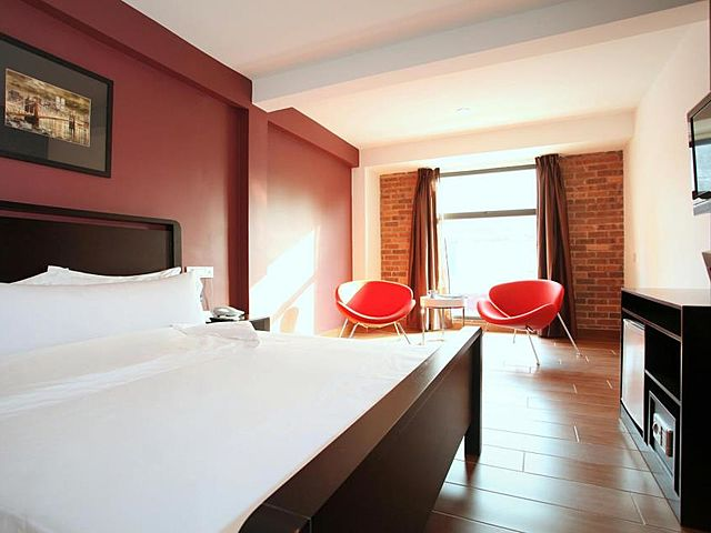minimalist hotel room with red and brick wall with two red chair