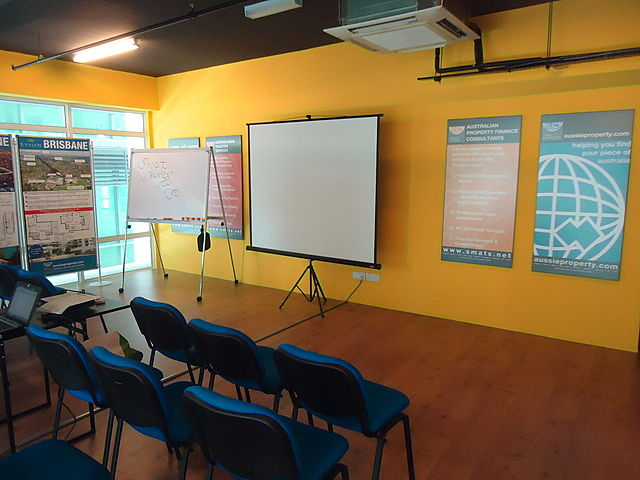 medium size seminar room in selangor with yellow wall and projector screen