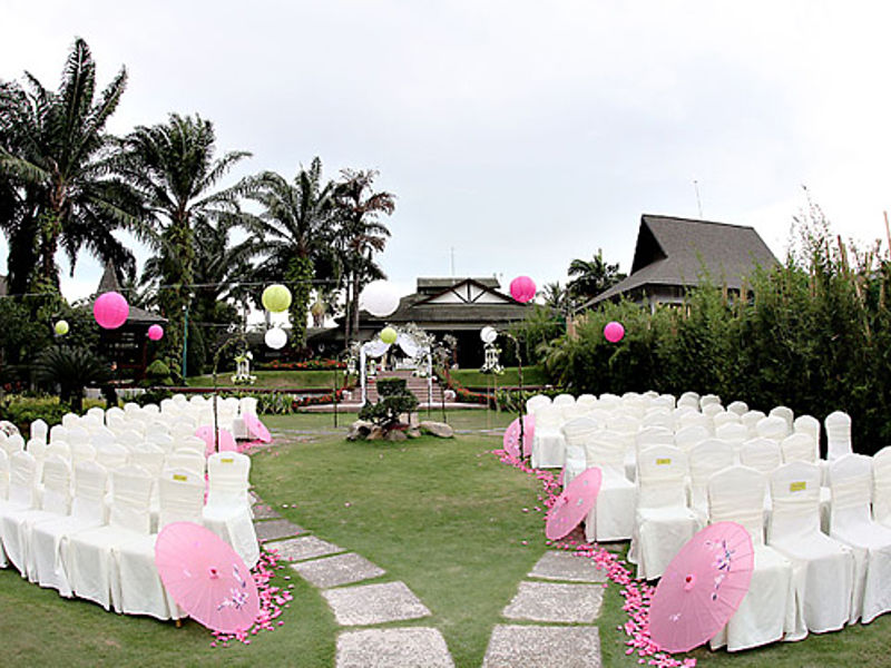 outdoor solemnisation decorate with white chairs and pink ballons