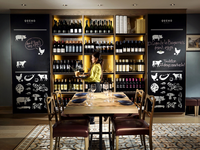 quemo private bar with wine shelves and dining table setting