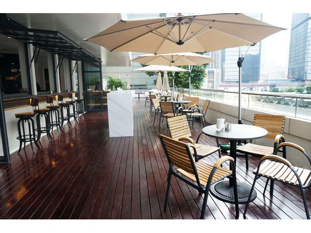 outdoor deck seating area with umbrella and bar seating