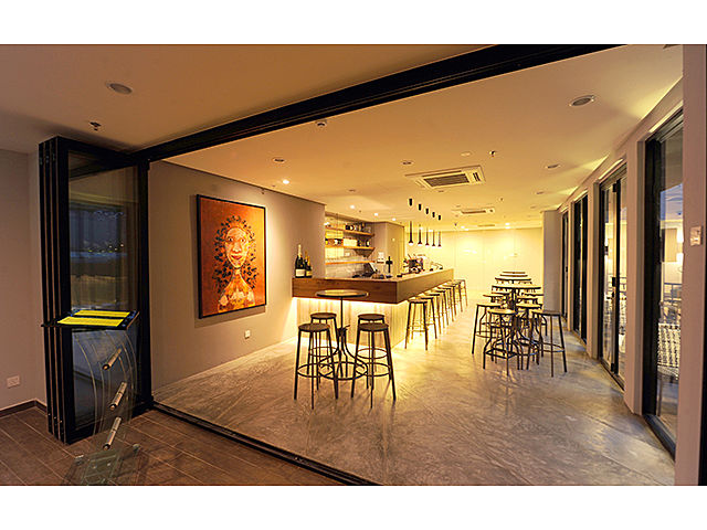 bar with 130 capacity with yellow lighting and glass door