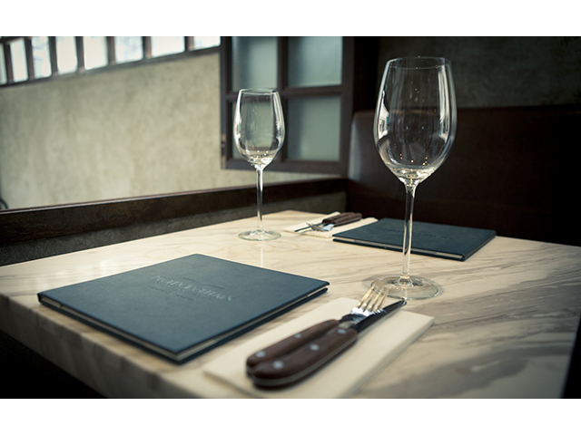 two wine glasses and menus on dining table