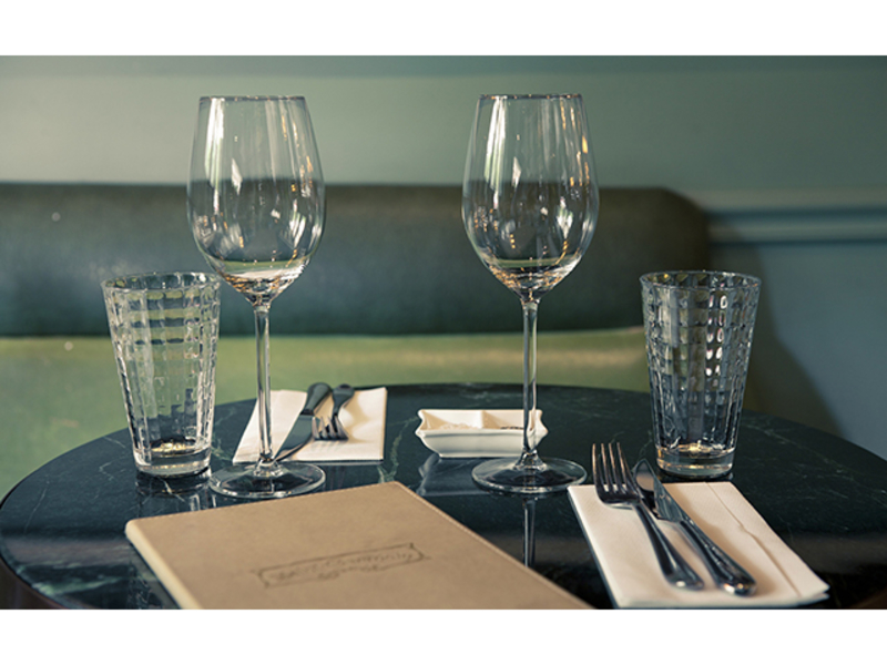 dining cutlery setting with wine glasses and menu on table