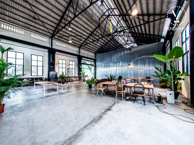 large workspace in Singapore with long wooden table and white floors
