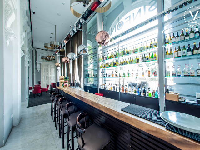 singapore white interior bar with high ceiling and long wooden table